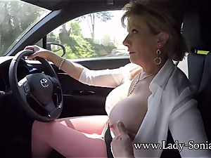 Mature nymph Sonia plays with her tits while driving